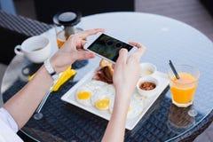 Mãos da mulher que tomam a foto do alimento pelo telefone celular Fotografia do alimento Pequeno almoço delicioso imagem de stock