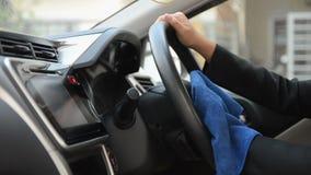 Mãos da mulher que usa a micro tela azul da fibra para limpar o carro video estoque