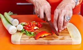 Mãos da mulher sênior que cortam vegetais Imagens de Stock Royalty Free