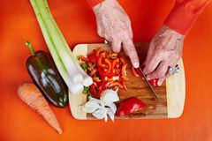 Mãos da mulher sênior que cortam vegetais Fotos de Stock Royalty Free