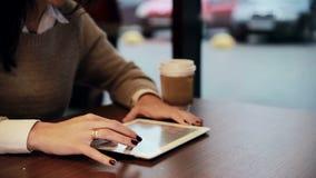 Mãos da mulher usando o écran sensível da tabuleta no café filme