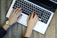 Mãos da mulher usando o portátil no fundo de madeira imagens de stock royalty free