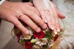 Mãos da noiva e de noivo com anéis de casamento Fotografia de Stock Royalty Free