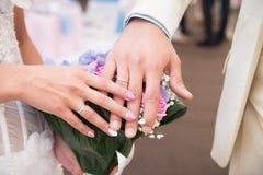 Mãos da noiva e do noivo com anéis de casamento celebrations Fotos de Stock Royalty Free