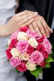mãos da noiva e do noivo que encontram-se no ramalhete fotografia de stock