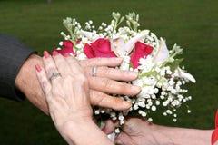 Mãos da noiva e do noivo que mostram anéis Imagens de Stock Royalty Free