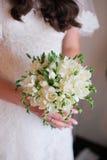 Mãos da noiva que guardam o ramalhete bonito do casamento fotografia de stock royalty free