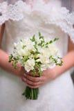 Mãos da noiva que guardam o ramalhete bonito do casamento fotografia de stock