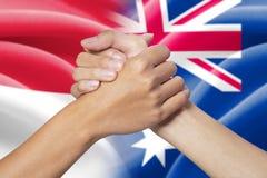 Mãos da parceria com as bandeiras indonésias e australianas Fotografia de Stock