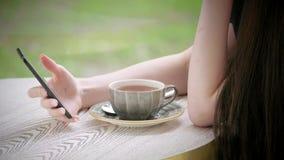 Mãos da parte do corpo do smartphone caucasiano novo da terra arrendada da menina à disposição Copo do chá no terraço do café da  video estoque