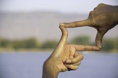 Mãos da pessoa que fazem a distância ou o símbolo do quadro na natureza imagens de stock royalty free