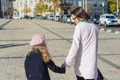 Mãos da posse da criança da mãe e da filha, caminhada e conversa na rua da cidade, vista da parte traseira foto de stock