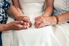 Mãos da posse da noiva e da avó no dia do casamento Imagens de Stock Royalty Free