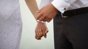 Mãos da posse dos noivos em uma caminhada do casamento filme