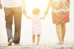 Mãos da terra arrendada da família na praia Imagens de Stock