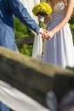 Mãos da terra arrendada da noiva e do noivo Imagens de Stock