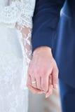 Mãos da terra arrendada da noiva e do noivo Fotos de Stock Royalty Free
