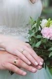 Mãos da terra arrendada da noiva e do noivo Foto de Stock