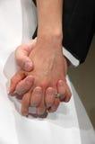 Mãos da terra arrendada do noivo e da noiva Imagem de Stock