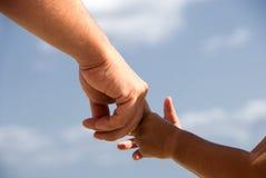 Mãos da terra arrendada do pai e do filho fotografia de stock