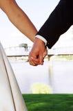 Mãos da terra arrendada dos pares do casamento Fotografia de Stock
