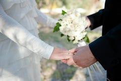 Mãos da terra arrendada dos pares do casamento Fotos de Stock Royalty Free