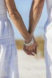 Mãos da terra arrendada dos pares em uma praia vazia Imagem de Stock Royalty Free