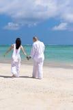 Mãos da terra arrendada dos pares na praia Imagens de Stock Royalty Free