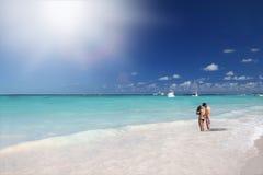 Mãos da terra arrendada dos pares na praia tropical no oceano fotos de stock royalty free