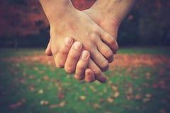 Mãos da terra arrendada dos pares no parque Fotos de Stock