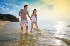 Mãos da terra arrendada dos pares que andam ao longo da praia Imagem de Stock