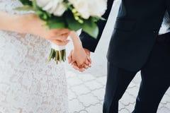 Mãos da terra arrendada da noiva e do noivo fotos de stock