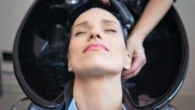 Mãos da vista superior do barbeiro profissional que lavam afastado a máscara do cuidado do cabelo da mulher video estoque