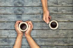 Mãos das canecas de café que guardam sobre a tabela de madeira Imagens de Stock