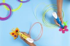 Mãos das crianças com as penas 3d e filamentos coloridos na tabela azul Foto de Stock Royalty Free