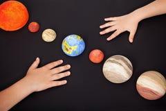 Mãos das crianças com os planetas do sistema solar Fotografia de Stock