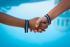 Mãos das crianças que agitam sobre o fundo da água azul fotografia de stock