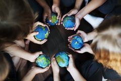 Mãos das crianças que mantêm as bolas colocando do globo unidas fotografia de stock