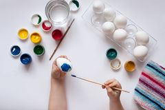 Mãos das crianças que pintam ovos no fundo branco Fotos de Stock Royalty Free