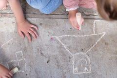 Mãos das meninas que tiram com giz branco Imagem de Stock Royalty Free