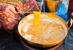 Mãos das mulheres adultas que fazem a sobremesa da tanga do foi imagem de stock