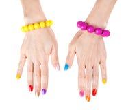 Mãos das mulheres com lustrador de prego multi-colored Foto de Stock Royalty Free
