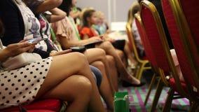 Mãos das mulheres com os dispositivos na conferência de negócio vídeos de arquivo