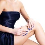 Mãos das mulheres com pregos azuis Imagens de Stock