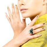 Mãos das mulheres com pregos dourados e esmeralda da pedra preciosa Fotografia de Stock Royalty Free