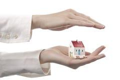 Mãos das mulheres com uma casa Imagens de Stock