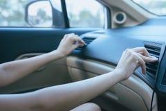 Mãos das mulheres que gerenciem sobre o sistema de condicionamento de ar do carro, botão no painel no painel do carro imagens de stock