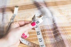 2016 mãos das mulheres que guardam costurar o centímetro Imagens de Stock Royalty Free