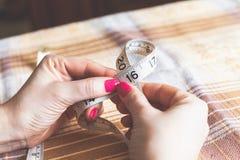 2016 mãos das mulheres que guardam costurar o centímetro Fotos de Stock