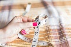 2016 mãos das mulheres que guardam costurar o centímetro Fotografia de Stock Royalty Free